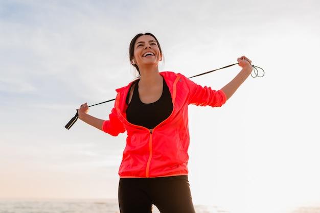 Giovane donna sottile attraente che fa esercizi sportivi all'alba del mattino sulla spiaggia del mare in abbigliamento sportivo, stile di vita sano, ascolto di musica sugli auricolari, indossa una giacca a vento rosa, tenendo la corda per saltare Foto Gratuite