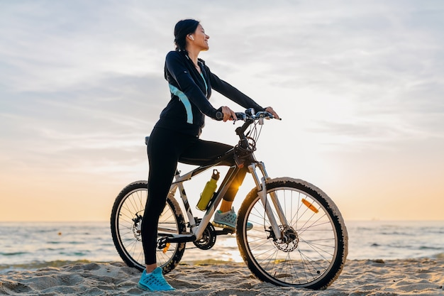 Young attractive slim woman riding bicycle, sport in morning sunrise summer beach in sports fitness wear, active healthy lifestyle, smiling happy having fun Free Photo