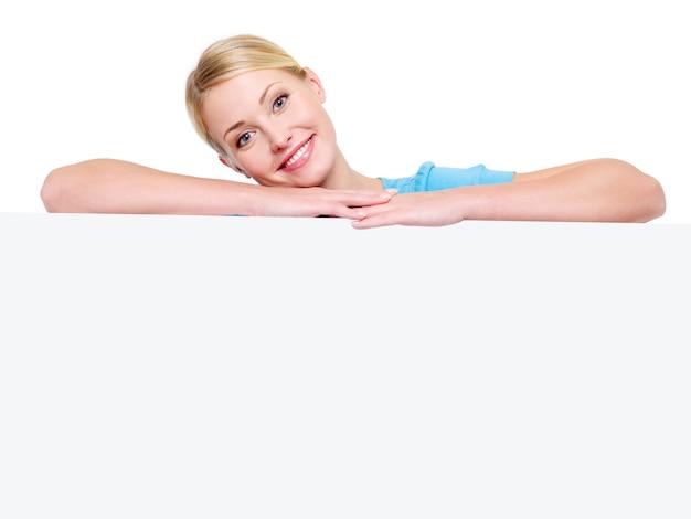 Giovane ragazza bionda sorridente attraente sotto il cartellone bianco Foto Gratuite
