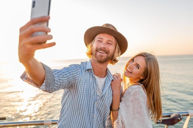 Молодой привлекательный улыбающийся счастливый мужчина и женщина, путешествующие на велосипедах, делающие селфи на камеру телефона, романтическая пара на берегу моря на закате, одежда в стиле хипстера в стиле бохо, друзья веселятся вместе Бесплатные Фотографии