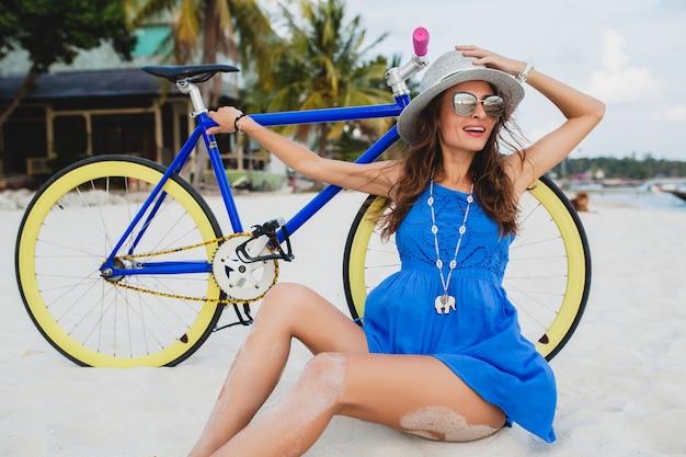 Giovane donna sorridente attraente in vestito blu che si siede sulla sabbia sulla spiaggia tropicale con la bicicletta che indossa cappello e occhiali da sole Foto Gratuite