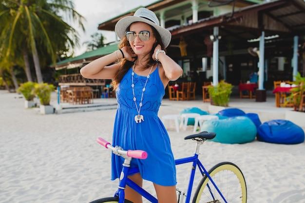 Giovane donna sorridente attraente in vestito blu che cammina sulla spiaggia tropicale con la bicicletta che indossa cappello e occhiali da sole Foto Gratuite