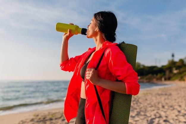 Молодая привлекательная улыбающаяся женщина занимается спортом в утреннем восходе солнца на морском пляже, держа коврик для йоги и бутылку воды, здоровый образ жизни, слушает музыку в наушниках, носит розовую ветровку Бесплатные Фотографии