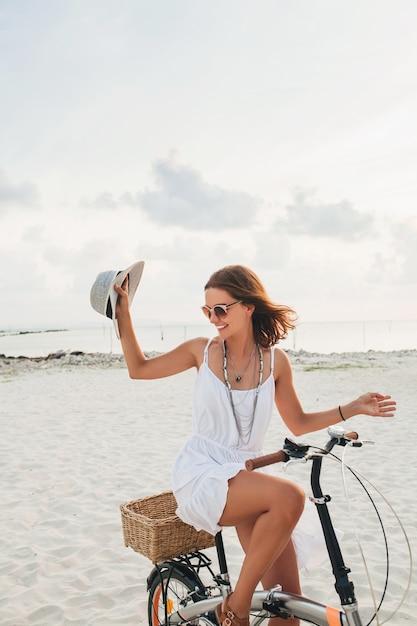 Giovane donna sorridente attraente in vestito bianco che guida sulla spiaggia tropicale in bicicletta che indossa cappello e occhiali da sole Foto Gratuite