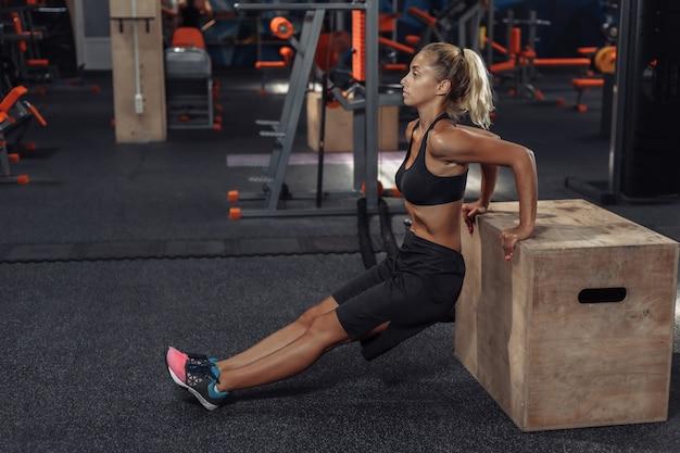 スポーツウェアの若い魅力的なスポーツ女性は、ジムで木箱で腕立て伏せを練習しています。機能トレーニングのコンセプト Premium写真