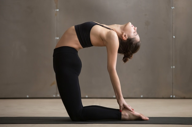 Young attractive sporty woman in camel pose, grey studio backgro Free Photo