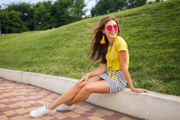 Young attractive stylish smiling woman having fun in city park, positive, emotional, wearing yellow top, striped mini skirt, pink sunglasses, white sneakers, summer style fashion trend, long legs Free Photo