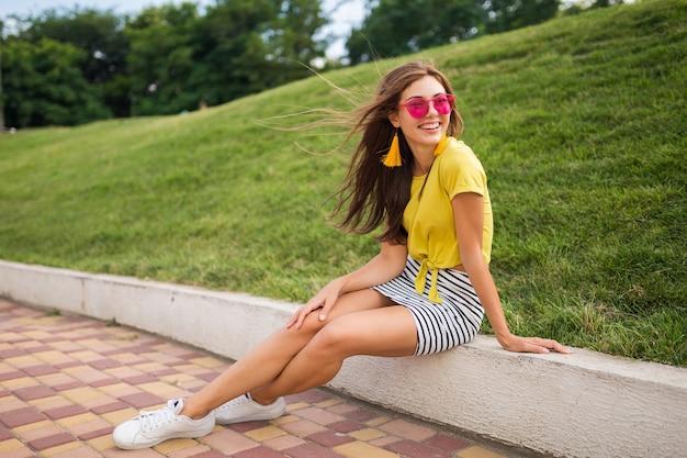 Giovane donna sorridente alla moda attraente che si diverte nel parco cittadino, positivo, emotivo, indossa un top giallo, minigonna a righe, occhiali da sole rosa, scarpe da ginnastica bianche, tendenza della moda in stile estivo, gambe lunghe Foto Gratuite