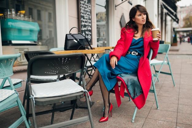 Молодая привлекательная стильная женщина, сидящая в городском уличном кафе в красном пальто, осенняя модная тенденция, пьющая кофе, в синем платье, туфли на высоких каблуках, ноги в черных чистых чулках, элегантная дама Бесплатные Фотографии