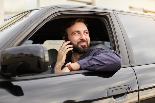 Giovane uomo barbuto di successo attraente in giacca blu e maglietta a righe, si siede al volante della macchina, chiama il cellulare, distoglie lo sguardo sognante e sorride. Foto Gratuite