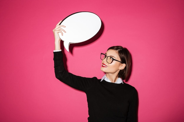 Young attractive thoughtful lady holding and looking at bubble speech Free Photo