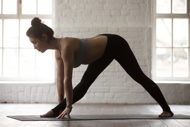 Young attractive woman in ardha parsvottanasana pose Free Photo