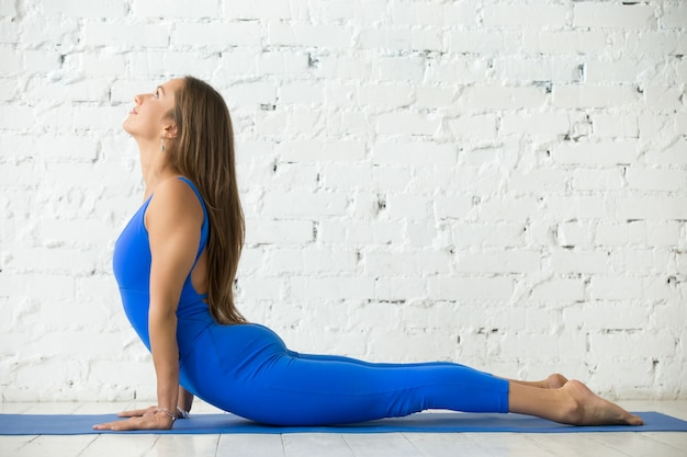 Young attractive woman in bhujangasana pose, white studio backgr