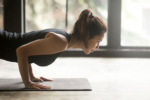 Young attractive woman in chaturanga dandasana pose Free Photo
