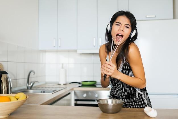 朝のキッチンでスクランブルエッグを調理する若い魅力的な女性、笑顔、幸せなポジティブな主婦、健康、ヘッドフォンで音楽を聴く、マイクのように泡立て器で歌う、楽しんで 無料写真