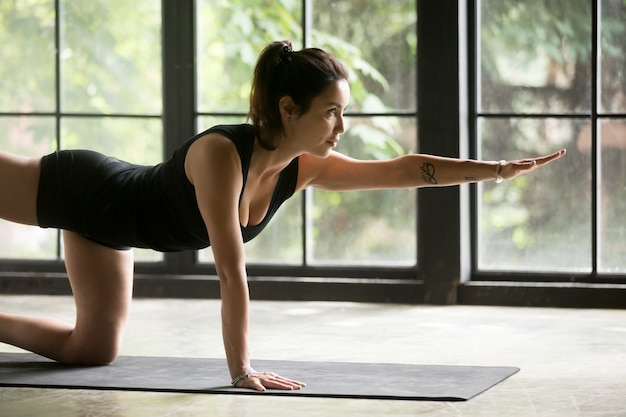 Young attractive woman doing donkey kick exercise Free Photo