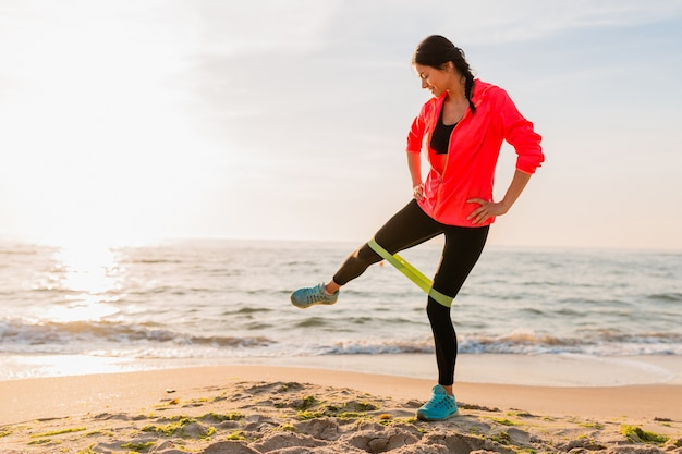 Young attractive woman doing sport exercises in morning sunrise on sea beach, healthy lifestyle, listening to music on earphones, wearing pink windbreaker jacket, making stretching in rubber band Free Photo
