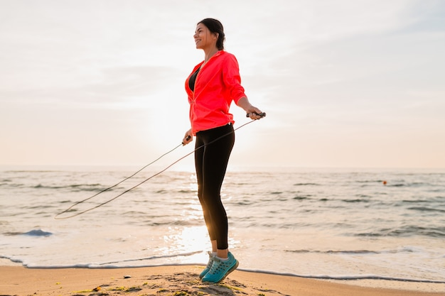 Young attractive woman doing sport exercises in morning sunrise on sea beach in sports wear, healthy lifestyle, listening to music on earphones, wearing pink windbreaker jacket, jumping in jump rope Free Photo