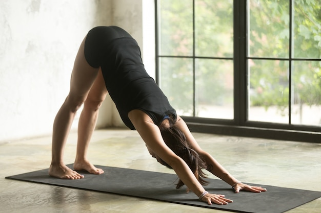 Young attractive woman in downward facing dog pose Free Photo