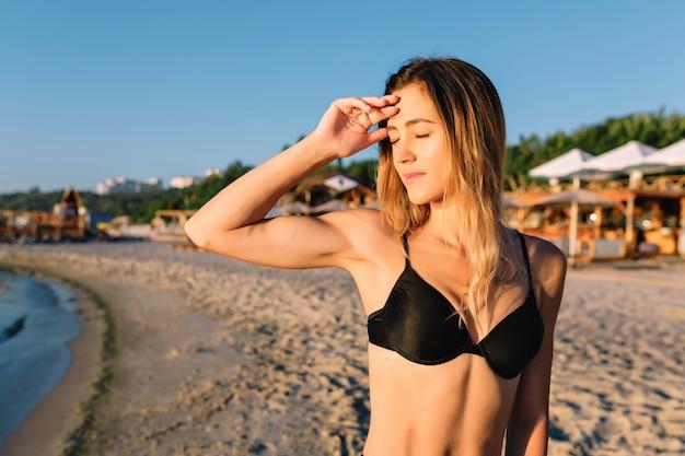 Giovane donna attraente vestita in costume da bagno nero sulla spiaggia di sabbia estiva Foto Gratuite