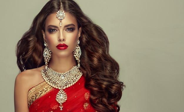 伝統的なインドの赤いショール(dupatta)と手作りの「クンダンスタイル」のジュエリーセットを身に着けた若い魅力的な女性。完璧で、密度が高く、波打つ、自由に飛ぶ髪と「スモーキーアイ」スタイルのメイク。 Premium写真