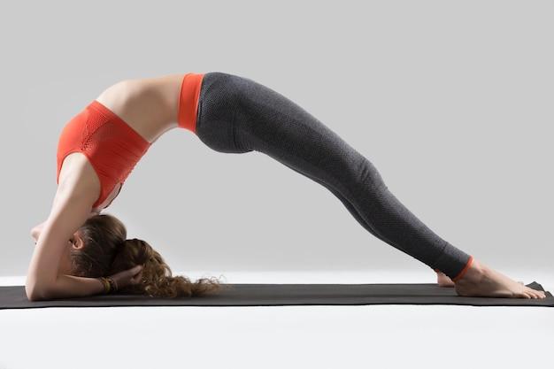 Young attractive woman in elbow bridge pose, grey studio backgro Free Photo