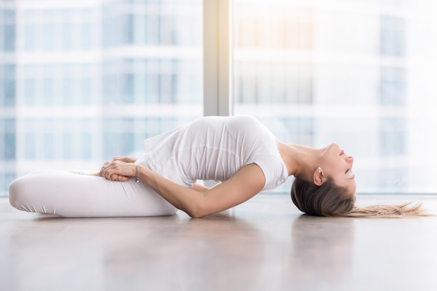 Young attractive woman in fish pose against floor window Free Photo