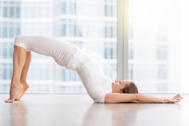 Young attractive woman in glute bridge pose Free Photo