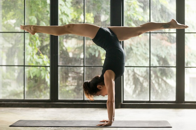 Young attractive woman in handstand pose, home background Free Photo