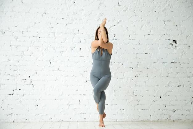 Молодая привлекательная женщина в garudasana pose, белая студия backgrou Бесплатные Фотографии