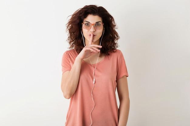 イヤホンで音楽を聴く、唇で指を押し、沈黙ジェスチャー、面白い驚きの感情、巻き毛、分離、ピンクのtシャツを示すメガネの若い魅力的な女性 無料写真