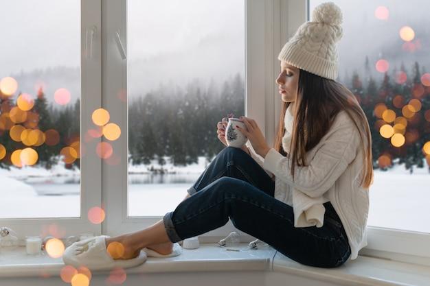 세련 된 흰색 니트 스웨터, 스카프와 모자 크리스마스 지주 컵에 창턱에 집에 앉아 젊은 매력적인 여자, 겨울 숲 배경보기, 조명 Bokeh 무료 사진