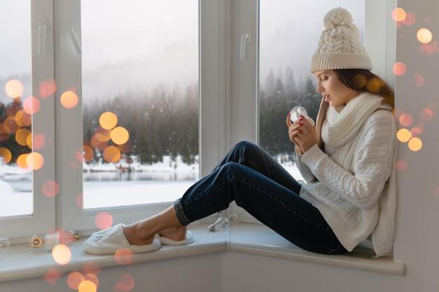 세련 된 흰색 니트 스웨터, 스카프와 모자 크리스마스 지주 유리 눈 공 선물 장식, 겨울 숲보기, 조명 Bokeh에 창턱에 집에 앉아 젊은 매력적인 여자 무료 사진