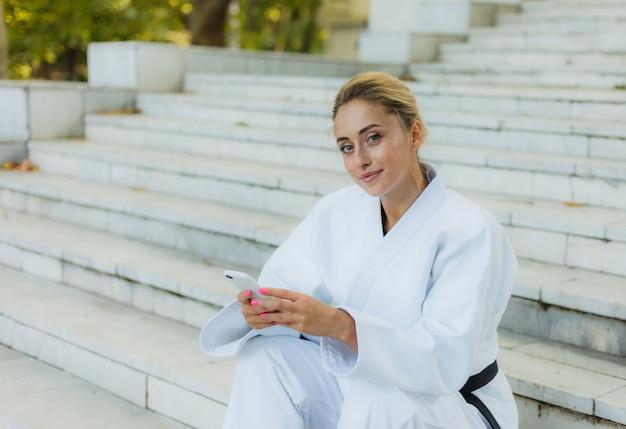 Молодая привлекательная женщина в белом кимоно с черным поясом. спортивная женщина сидит на лестнице и использует смартфон на открытом воздухе. отдых после тренировки. боевые искусства Premium Фотографии