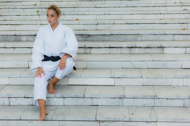 Молодая привлекательная женщина в белом кимоно с черным поясом. спортивная женщина сидит на лестнице на открытом воздухе. боевые искусства Premium Фотографии