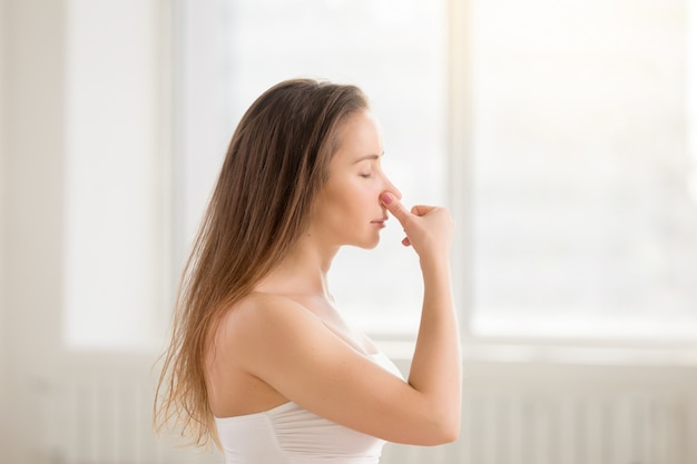 Young attractive woman making alternate nostril breathing, white Free Photo