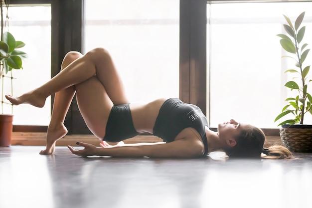 Young attractive woman in matsyasana pose, home interior backgro Free Photo