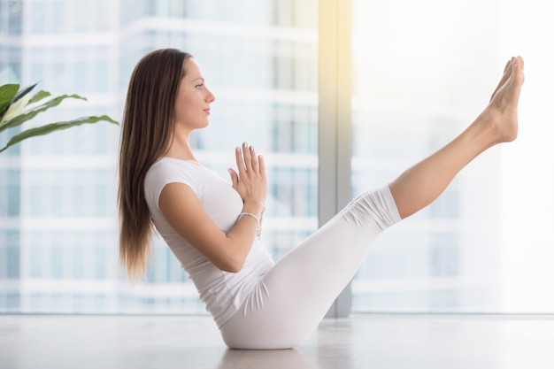 Young attractive woman in paripurna navasana pose against floor window Free Photo