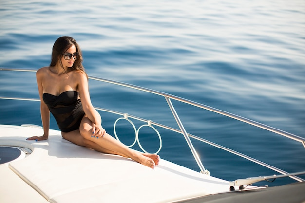 Young attractive woman poses on  luxury yacht floating on sea Premium Photo