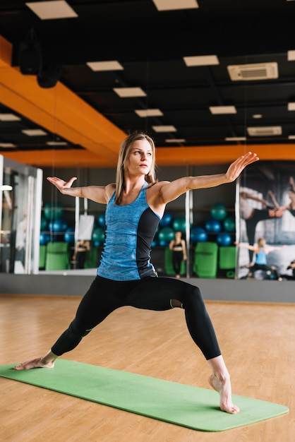 Young attractive woman practicing yoga on green mat in fitness gym Free Photo