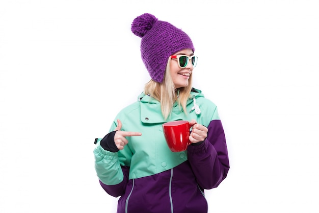 Young attractive woman in purple ski suit hold red cup Premium Photo