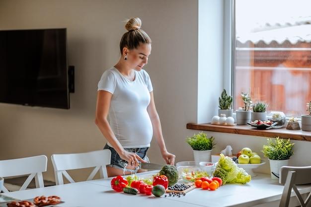 白いシャツとジーンズのショートパンツのポーズで若い魅力的な女性の妊娠中の体 Premium写真