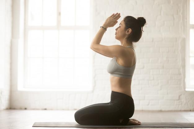 Young attractive woman in seiza pose, white loft studio Free Photo