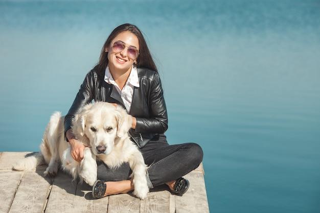 Молодая привлекательная женщина, сидя на пирсе со своей собакой. лучшие друзья на природе Premium Фотографии
