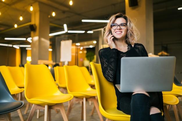 講堂に座っている若い魅力的な女性、ラップトップに取り組んで、眼鏡をかけて、多くの黄色い椅子、オンラインの学生教育、フリーランサー、笑顔、スマートフォンで話している、楽しみ、スタートアップ 無料写真
