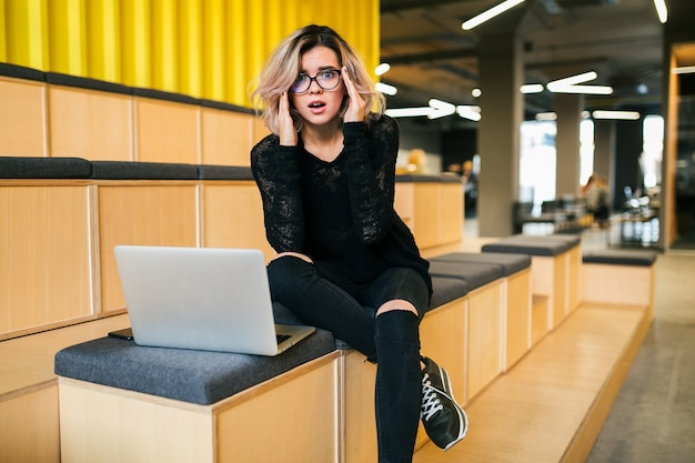 Young attractive woman sitting in lecture hall, having stress, working on laptop, wearing glasses, modern auditorium, student education online, freelancer, busy, headache, frustrated face expression Free Photo