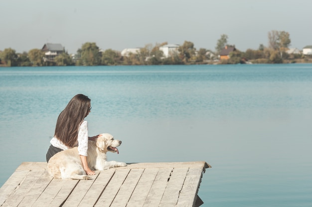 Young attractive woman sitting at the pier with her dog. best friends outdoors Premium Photo