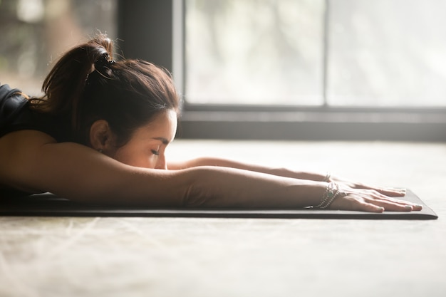 Young attractive woman stretching on the floor Free Photo