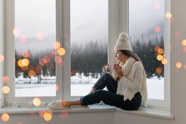 Giovane donna attraente in elegante maglione lavorato a maglia bianco, sciarpa e cappello seduto a casa sul davanzale della finestra a natale che tiene tazza bere tè caldo, vista sullo sfondo foresta invernale, luci bokeh Foto Gratuite