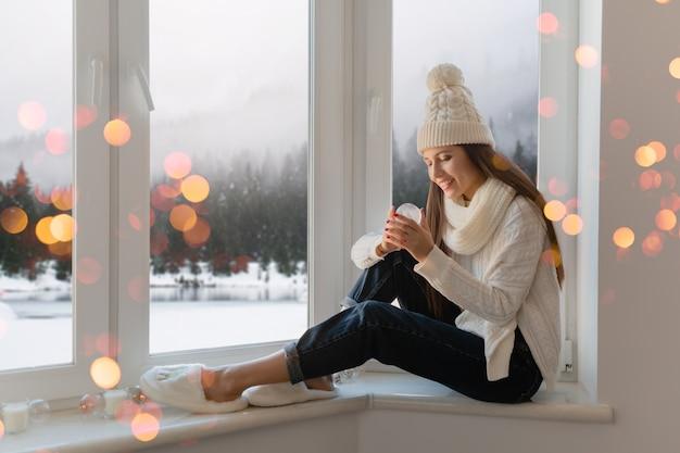 Giovane donna attraente in elegante maglione lavorato a maglia bianco, sciarpa e cappello seduto a casa sul davanzale della finestra a natale che tiene la decorazione presente della palla di neve di vetro, vista della foresta di inverno, bokeh delle luci Foto Gratuite